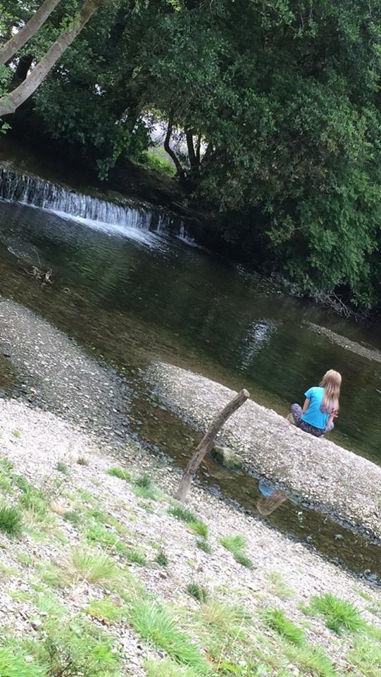 child sitting next to riverbank in Kilbrittain