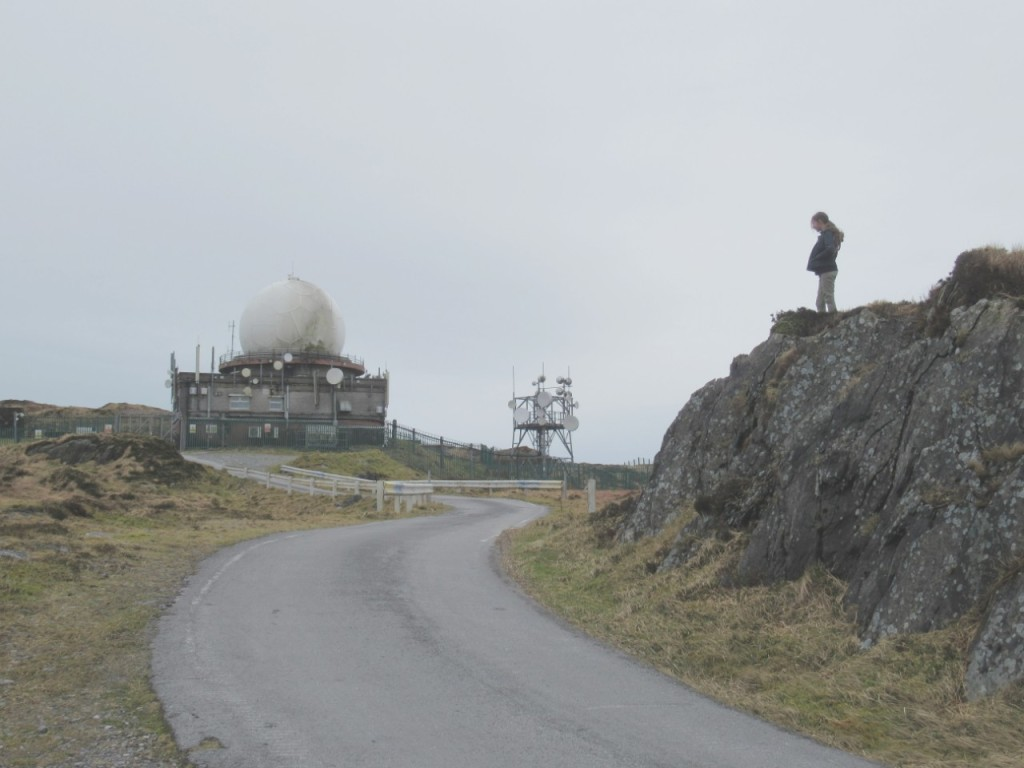 Child standing on rock near radar dome on mount gabriel